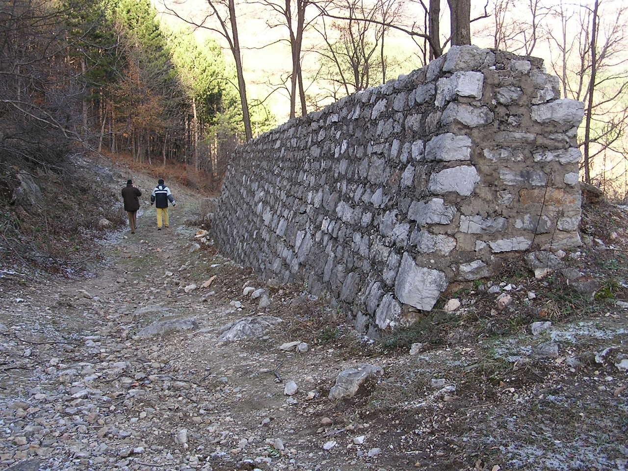 Portion of the containment wall constructed for diverting the course of the stream so that it could pass upstream of the dam. Today this stream flows once more in its original bed at the bottom of the valley.
