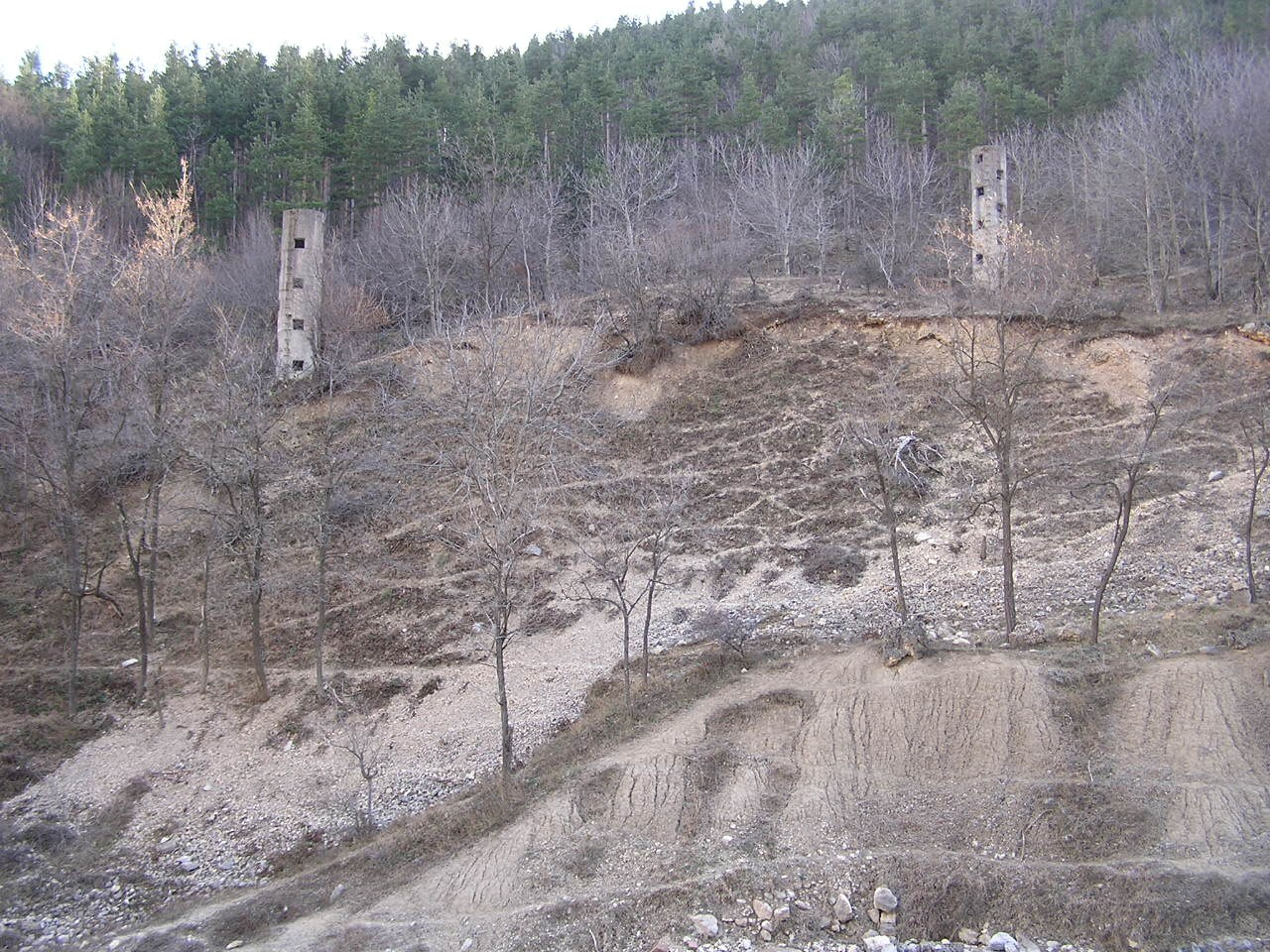 Detail of the area where the tailings dam stood. In the foreground some accumulations of consolidated muds and, in the background, two of the overflow towers built expecting a further increase of the embankment. Two rows of overflow towers were constructed: the second row (photo) was never used because the embankment collapsed before the level of the stored waste muds could reach that height.