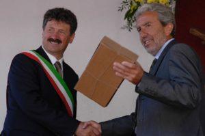 Il sindaco di Tesero Gianni Delladio consegna il riconoscimento all'allora capo della Protezione Civile Trentina Claudio Bortolotti.